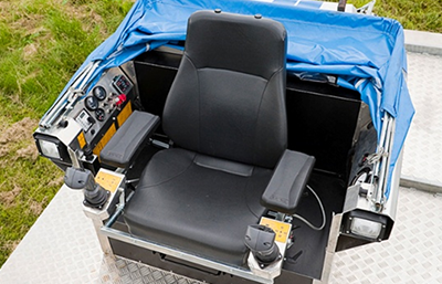 Ergonomic operator's seat with joysticks for operation/control of the machine and its tools.